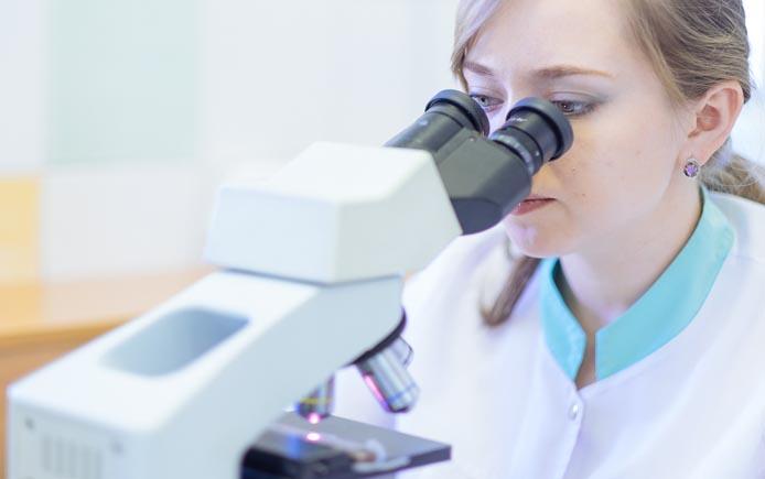 Доктор изучает мазок под микроскопом
